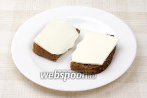 На кусочки чёрного хлеба выложить ломтики фетаксы.