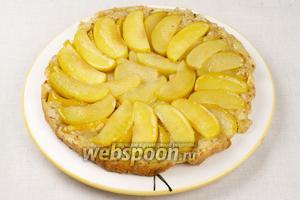 Готовый пирог вынуть из формы и перевернуть яблоками вверх, затем дать постоять 10-15 минут, чтобы яблочный сок пропитал корж. Подавать тёплым.
