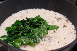 В готовый рис выложить шпинат, хорошо всё перемешать.