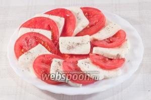 Поочерёдно разложите друг на друга помидоры и сыр. Приправьте молотым перцем и солью.