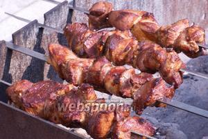 Разместить мясо на мангале и постоянно прокручивать, чтобы шашлык равномерно прогревался и румянился.