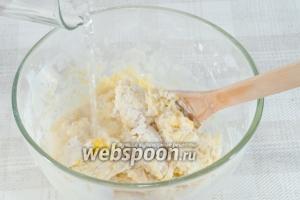 Затем понемногу вливайте воду. Вымешивайте тесто руками, оно должно получиться мягкое и эластичное, не пристающее к рукам.