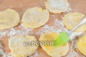 Разделите тесто на 8 кусочков. Сливочное масло растопите. Каждый кусочек приплюсните рукой в лепёшку и смажьте сливочным маслом.