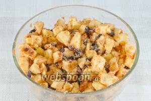 Сделайте начинку. Яблоки очистите от кожуры и семечек, нарежьте кубиками, смешайте их с изюмом, сахаром и панировочными сухарями.