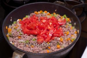 Когда фарш изменит цвет (станет белым), добавить порезанные помидоры и хорошо всё перемешать.