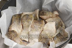 Филе судака помыть, обсушить, порезать на порционные куски.   Сковороду застелить пергаментной бумагой и выложить в неё рыбу.