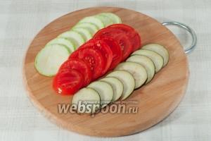 Нарежьте кружочками кабачки, помидоры и баклажаны.