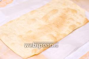 Вместе с пергаментом выкладываем корж на противень и выпекаем в разогретой до 180°С духовке до появления золотисто-коричневых пятен.