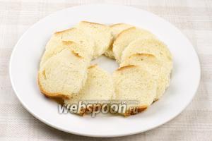 Батон нарезать ломтиками, а затем стаканом выдавить кружки — основу для закуски, получилось 10 кусочков.
