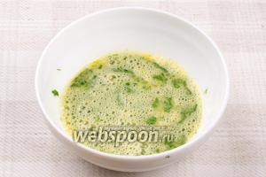 Взбить вилкой 2 яйца, добавив 2/3 зелени, щепотку соли и чёрного молотого перца.