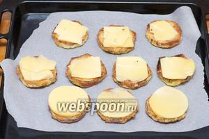 Застелить противень пергаментной бумагой и выложить кусочки батона, а на них сыр.