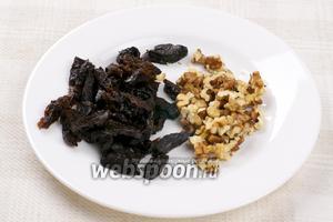 Чернослив хорошо помыть, удалить косточки и порезать, орехи тоже порезать.
