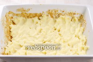 Форму смазать сливочным маслом и присыпать панировочными сухарями. Выложить на дно половину пюре.