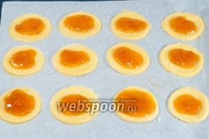 На противень выстланный пекарской бумагой выложите сначала целые кружочки. Сверху чайной ложкой немного джема, не доходя до краёв примерно 0,5 см.