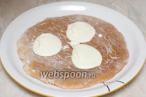 Выложить первый корж на блюдо и добавить 3 полные столовые ложки крема.