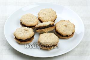 Нижнюю часть печенья смазываем приготовленной шоколадной начинкой и скрепляем с другой. Так приготовить всё печенье.
