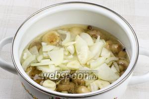 Готовые грибы переложить в небольшую кастрюлю, добавить порезанные лук и чеснок.