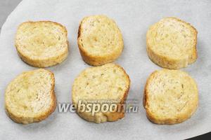 Обмакнуть каждый ломтик хлеба в оливковое масло и выложить на противень, застеленный пергаментной бумагой.
