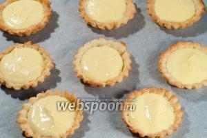 Готовые корзинки достаньте из формочек и наполните их лимонным кремом.