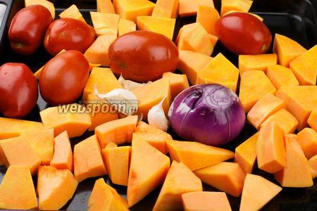 Тыкву (1 кг) очистить от семян и кожуры и порезать на средние куски, 500 грамм помидоров хорошо помыть, 1 луковицу очистить и надрезать, 5 зубчиков чеснока не очищать — всё овощи выложить на противень.