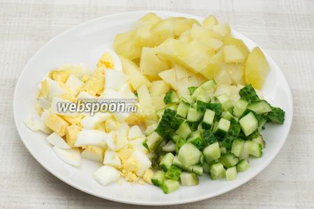 Яйца предварительно отварить вкрутую (опустить в холодную воду, довести до кипения и варить 10 минут с момента закипания). Картофель так же отварить в мундире до готовности 15-20 минут.  Картофель, яйца и огурцы порезать кубиками.