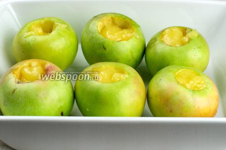 Выложить яблоки на противень или в форму и добавить по 2 чайные ложки мёда.
