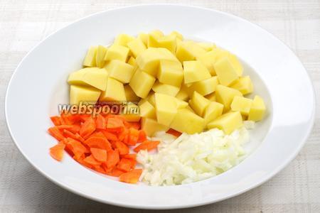 Овощи очистить и помыть. Картофель нарезать кубиками, морковь кружочками, которые поделить на 4 части. Лук мелко нарезать.