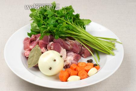 Свиные рёбрышки помыть и порезать на порции. Петрушку помыть, чеснок очистить, морковку почистить и порезать крупными кольцами, луковицу почистить и воткнуть в неё гвоздику.