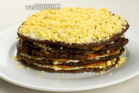 Сварить 2 яйца вкрутую (10 минут с момента закипания), желтки размять вилкой и присыпать ими верхний корж печеночного торта. Дать пропитаться торту 1-2 часа.