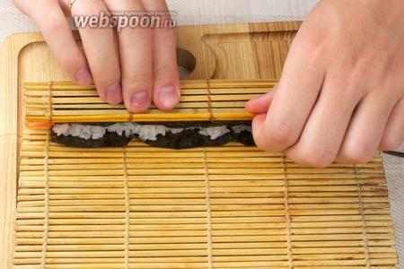 Закрутить ролл с помощью коврика, хорошо уплотняя рис и придавая ему форму.