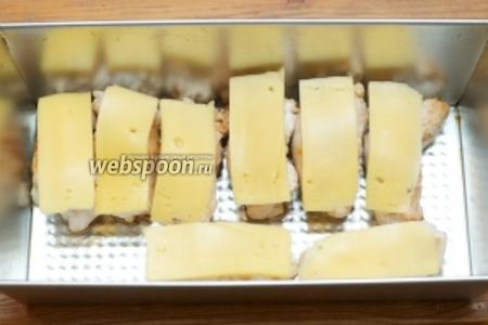 Из обжаренных рулетиков удалить зубочистки. В форму для  запекания добавить 1 ст. л. растительного масла и выложить мясо. Затем каждый рулет накрыть кусочком сыра.