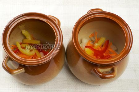 На дно каждого горшочка влить по 1-2 столовой ложке растительного масла, а затем добавить по щепотке лука, моркови и сладкого перца.