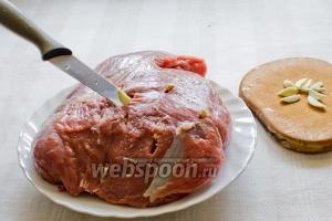 Перед тем, как замариновать мясо — нашпиговываем его чесноком.  Для этого нарезаем соломкой зубчики чеснока,ножом делаем отверстия и в них вкладываем чеснок.