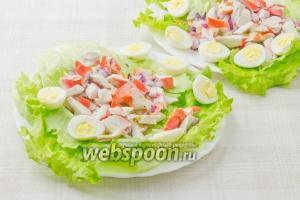 Теперь осталось промыть салатные листья, обсушить и разложить их по сервировочным тарелкам. Сверху поместить смесь крабовых палочек и лука. Полить заправкой и украсить перепелиными яйцами.  Ваш салат готов!