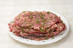 Теперь замаринуйте мясо. Мы делаем это так: кладём кусок отбивной и только верхнюю его часть солим, перчим, посыпаем розмарином. Сверху кладём следующий кусок и так все отбивные выкладываем в столбик и на пару часов отправляем в холодильник мариноваться.