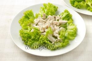 Разложите куриное филе на листья салата.