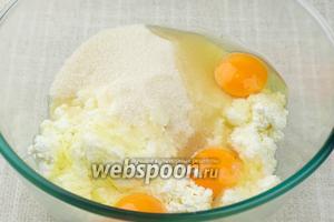В глубокой миске соединить сахар, творог и яйца — перемешать всё в однородную массу.