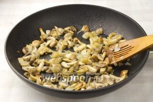 Разогрейте сковороду, налейте пару столовых ложек масла и обжаривайте лук и шампиньоны 5 минут.