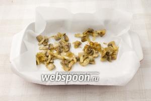 По желанию застелите форму пергаментной бумагой. Выложите половину обжаренных грибов с луком.