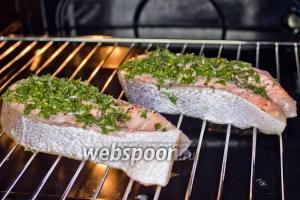 Рыбу положите на решётку, подложите под неё противень, чтобы было куда стекать жиру. Включите режим «гриль» и запекайте 15 минут при 200 °С.