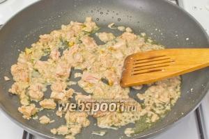 Слейте жидкость из банки с тунцом и выложите на сковороду. Разомните вилкой рыбные кусочки. Обжаривайте тунец 5 минут, постоянно перемешивая.