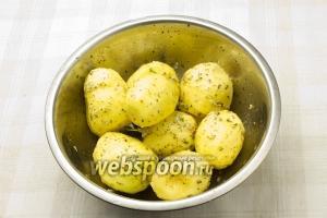 Положите картофель в миску с маслом и специями. Тщательно перемешайте.