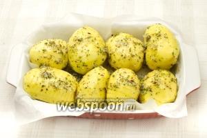 Выложите картофель в форму, застеленную пергаментной бумагой, полейте оставшимся маслом. Поставьте в разогретую до 180 °С духовку. Запекайте 30 минут.
