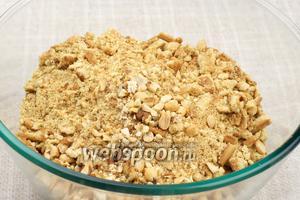 Печенье разломать руками в крошку и добавить орехи, которые предварительно крупно порубить.