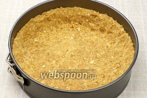 В разъёмную форму диаметром 22 см, выложить массу и сформировать корж с бортиками высотой не менее 2 см. Поставить в холодильник на время приготовления начинки.