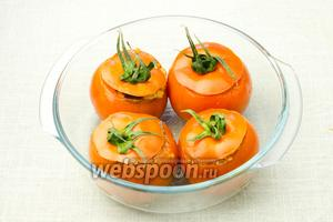 Дно формы для выпекания смажьте оливковым маслом. Выложите в неё помидоры, накройте их крышечками и выпекайте в разогретой до 150 °С духовке 20-30 минут.