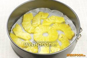 Дно формы (21-22 см) застелить пергаментом, затем смазать сливочным маслом и выложить дно ананасами (можно в два слоя).