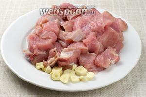 Индюшиное филе хорошо помыть и нарезать крупными кусками, чеснок очистить и нарезать пластинами.