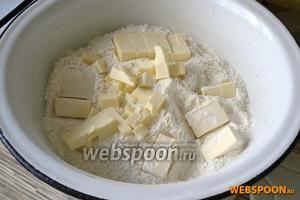 Просеять в миску муку. Нарезать маленькими кубиками холодное масло и быстро перетереть в крошку. По одной ложке добавлять ледяную воду и тщательно, но быстро перемешивая, замесить тесто. Скатать тесто в шар и отправить в холодильник на 30 минут.