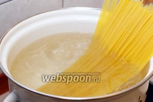 Довести воду до кипения (из расчёта на 100 г спагетти 1 л воды), добавить 1-2 ст. л. оливкового масла и отварить спагетти до состояния аl dente.